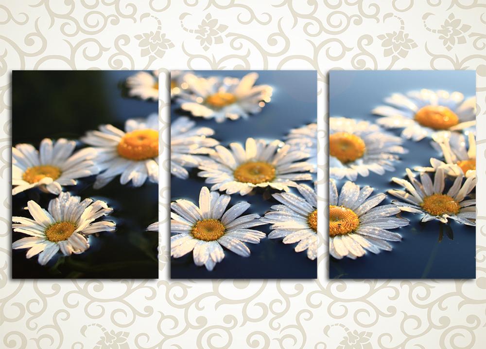 Модульная картина Цветы ромашкиЦветы и фрукты<br>Светлая и позитивная модульная картина «Цветы ромашки» станет прекрасным дополнением интерьера прихожей, гостиной, зала, спальни и кухни. Она изображает солнечные желто-белые цветы на темном фоне, изображение состоит из 3 вертикальных модулей. Каждый сегмент вручную обтянут холстом, что обеспечивает максимально естественное восприятие изображения.<br>