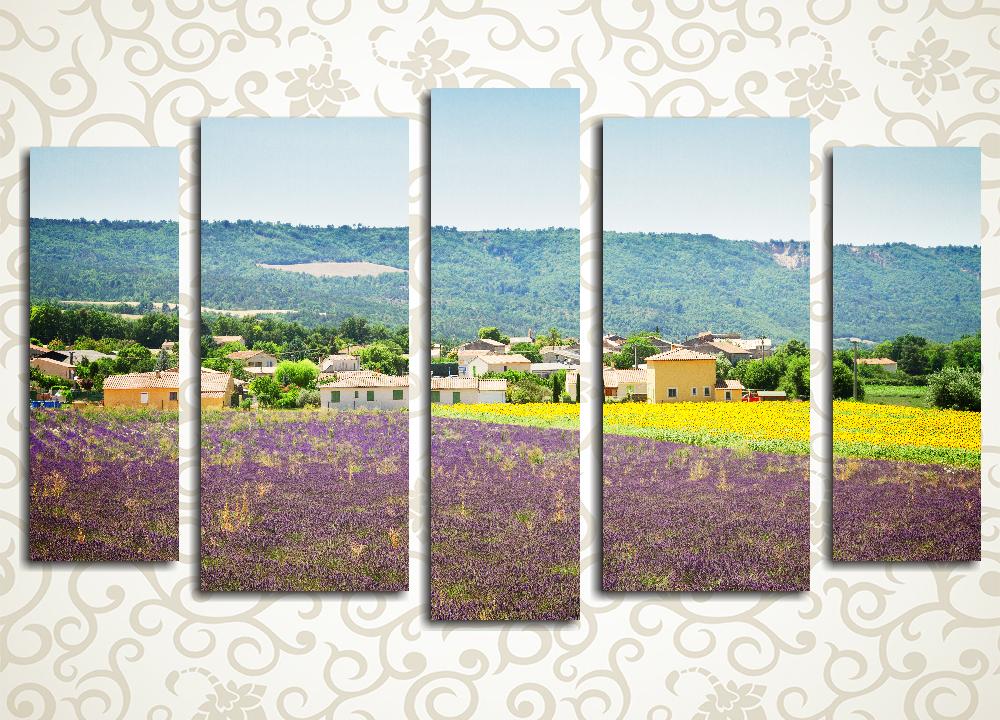 Модульная картина Лавандовое полеТолько в глубинке Франции можно встретить лиловое поле. Именно такой необычный пейзаж запечатлен на модульной картине «Лавандовое поле». Композиция из 5 фрагментов гармонично сочетает в себе самые яркие оттенки лета: сочную зелень, нежно-лиловые и ярко-желтые цветы, теплые песочные оттенки небольшого городка и прозрачную голубизну неба. Она позволит создать яркий, но ненавязчивый акцент в интерьере спальни, гостиной, столовой или кухни. Такой декор не только позволяет добавить неповторимую нотку в обстановку, но и существенно увеличивает пространство помещения, делая его светлее и уютней.<br>